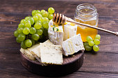istock Various sorts of cheese, grapes and honey 813279384