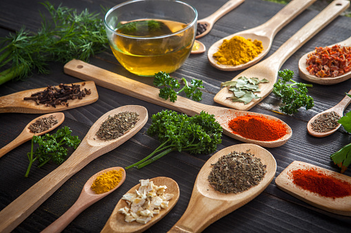 Various spice and wooden spoons with herbs and olive oil on wooden table