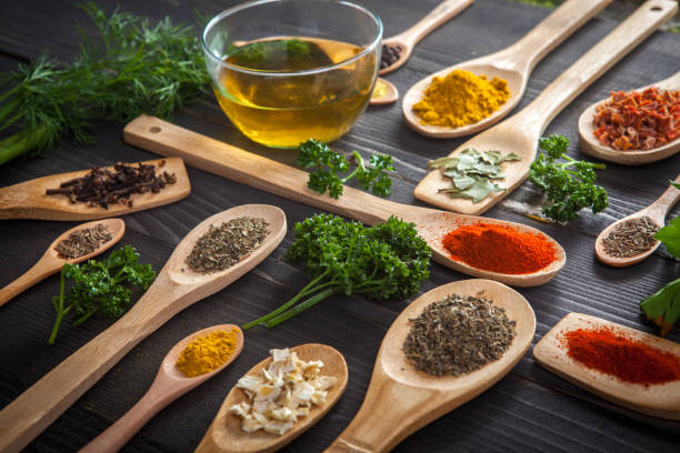 Various spice on wooden spoons with herbs stock photo