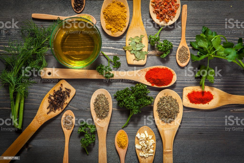 Various spice on wooden spoons with herbs foto stock royalty-free
