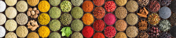 various spices and herbs as a background. colorful condiments in cups, top view - spezia foto e immagini stock