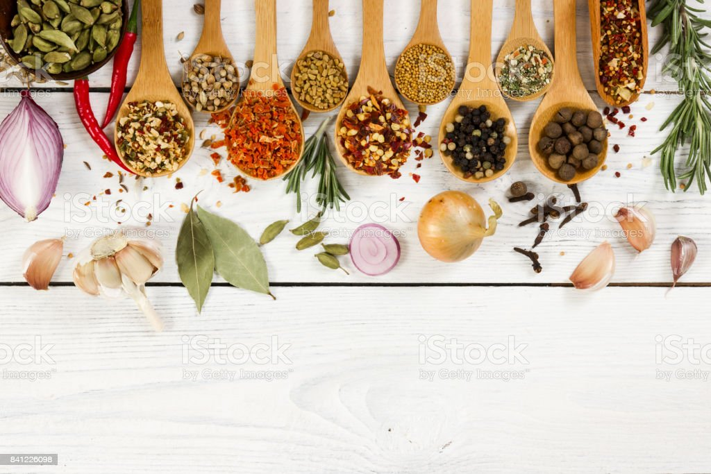 Various spices in wooden spoon on light background. stock photo