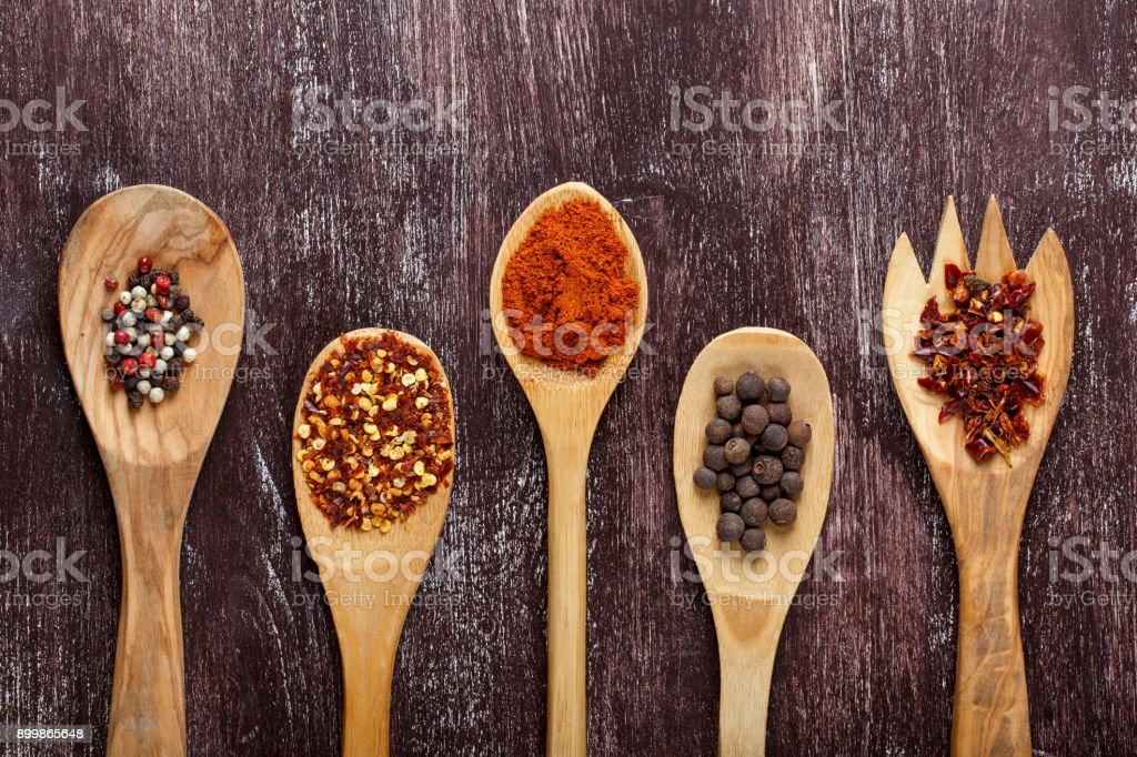 Various spices in wooden spoons on dark brown background. Different types of paprika and peppercorn. Top view. stock photo