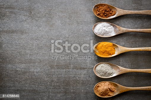 Various spices on wooden spoons. Food ingradients.