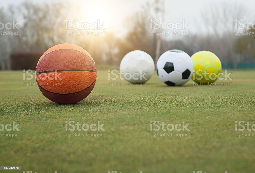 Various sports balls on grass field foto