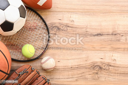 Sports background.  Tennis, basketball, soccer, baseball, and football sport balls and equipment on wooden background.  Copy space at side.