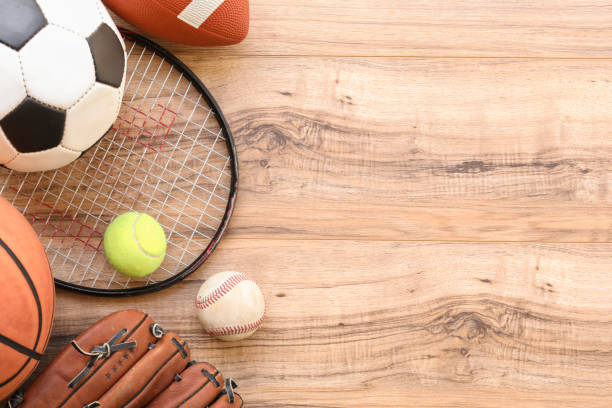 Various sports equipment, balls on wooden background. stock photo