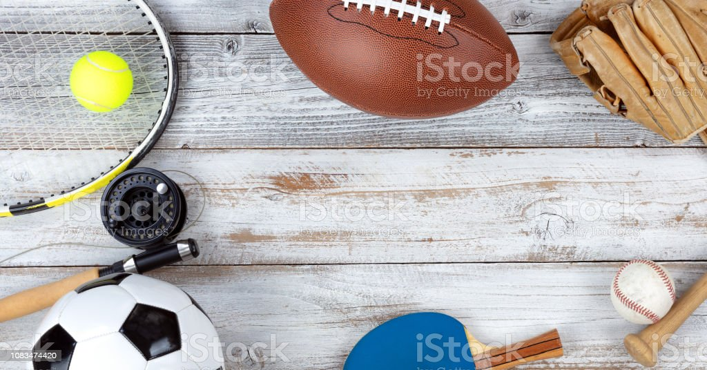 Various sports equipment on white rustic wooden background stock photo