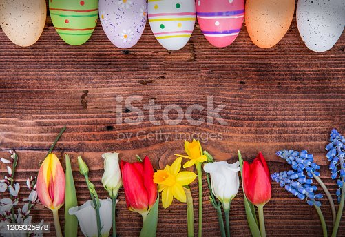 921112244 istock photo Various Spring Flowers and Easter Eggs on Wooden Background 1209325978