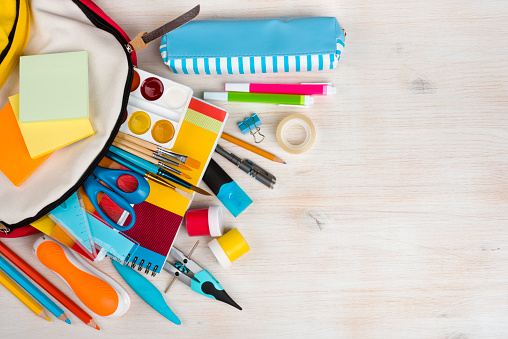 Various stationery school and office supplies over wooden texture background
