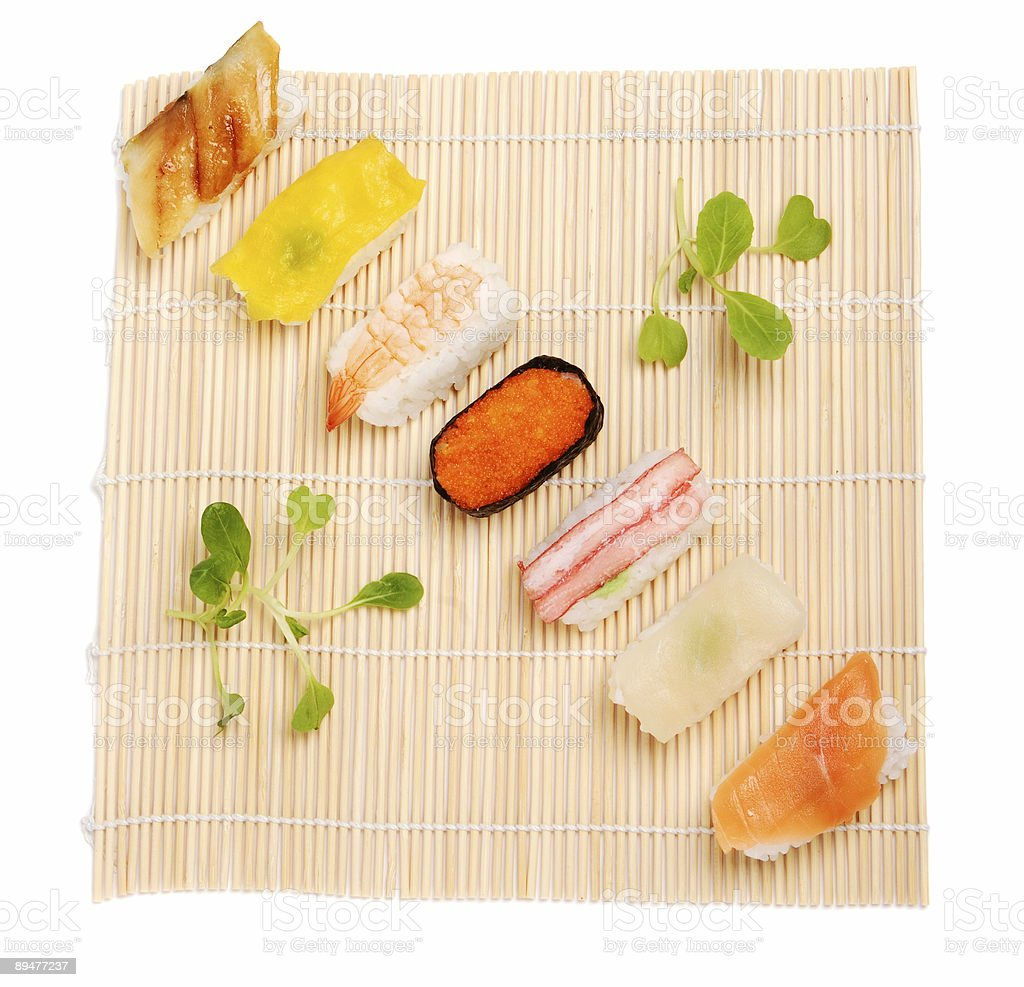 Various sushi and green arranged on bamboo mat royalty-free stock photo