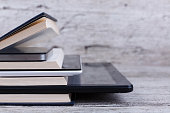 Various modern tablets are among a stack of different books. On a wooden background. The concept of knowledge. Close-up.