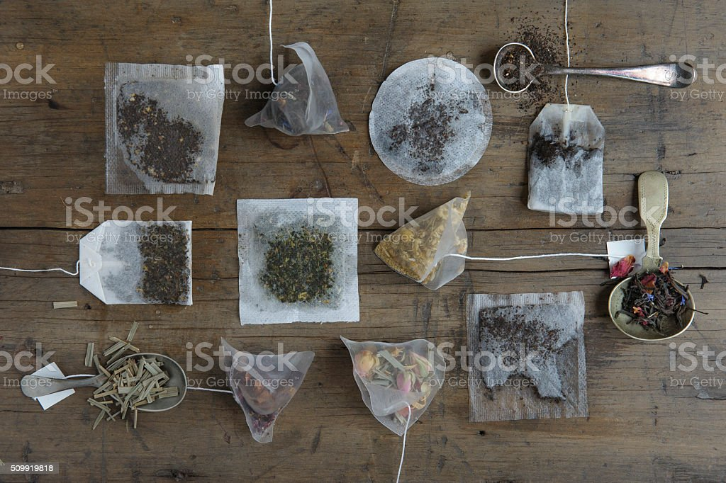 Various tea bags on a wooden board stock photo