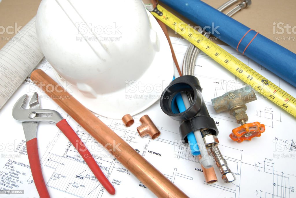 Various tools for plumbing laid atop blueprints royalty-free stock photo