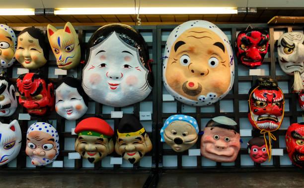 各種販売のための市場の木製の壁に掛かっている伝統的なイベントの日本で創造的な古代紙マスク - 伝統的な祭り ストックフォトと画像