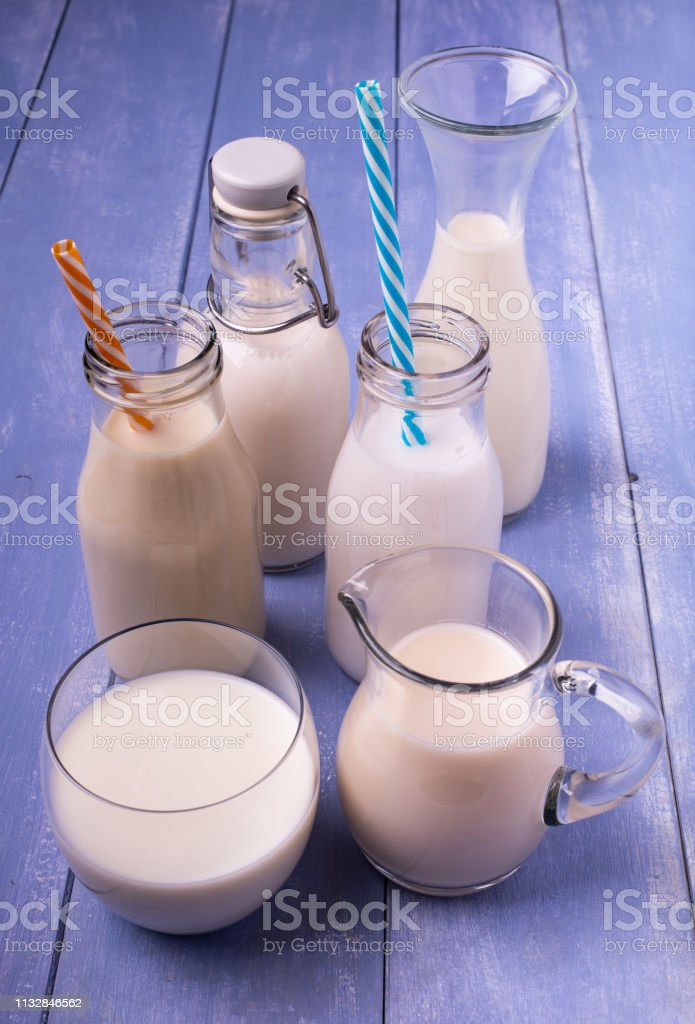 types of vegetable and organic milk in glass containers on a light...