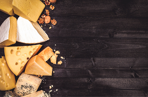 Various types of cheese on black wooden background with copy space. Cheddar, parmesan, emmental, blu cheese. Top view, photo filtered in vintage style