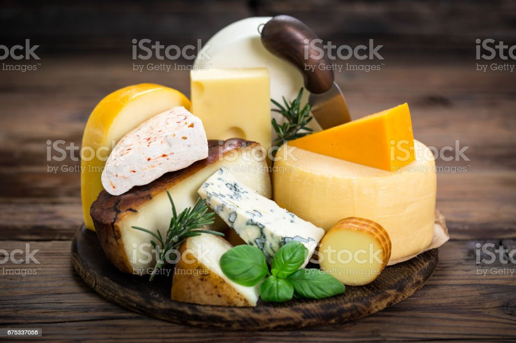 Various types of cheese on the wooden table stock photo