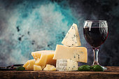 Various types of cheese and red wine still life on wooden table