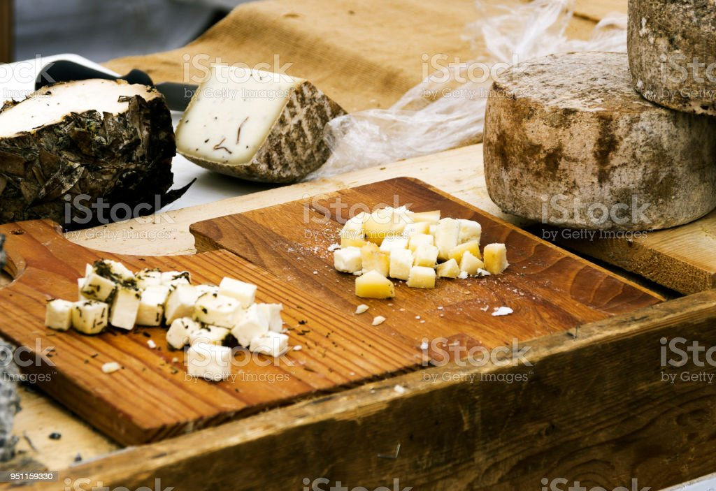 Various types of cheeses, on wooden cutting board, and rustic table in outdoor market. - foto stock