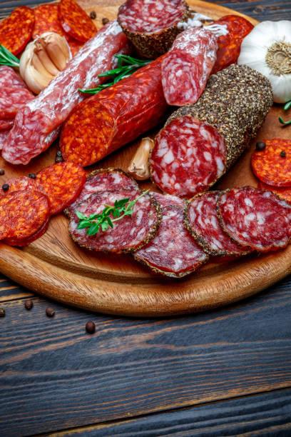verschiedene arten von getrockneten bio salami wurst auf holzbrett - pökeln stock-fotos und bilder
