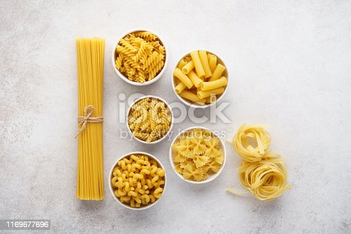 istock Various types of dry pasta in bowls on light gray background. 1169677696