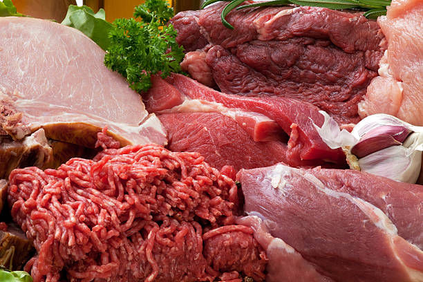 Various types of fresh raw meat piles stock photo