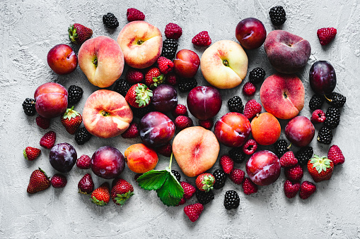 Top view of various types of tropical fruits on white background. Directly above shot of a blackberries, raspberries, strawberries, plums, peaches, apricots and apples.