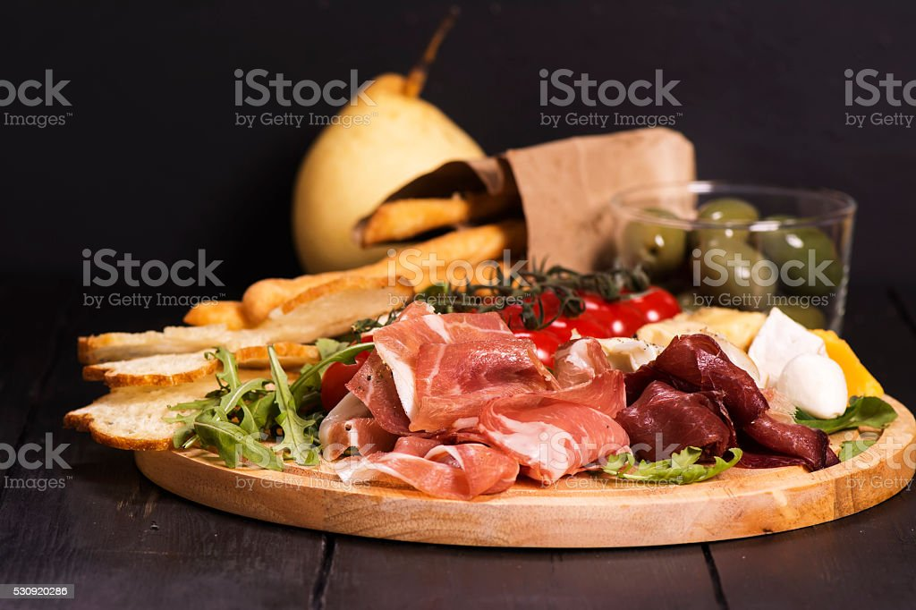 Various types of italian appetizers: ham, cheese, grissini, olives, fruits stock photo