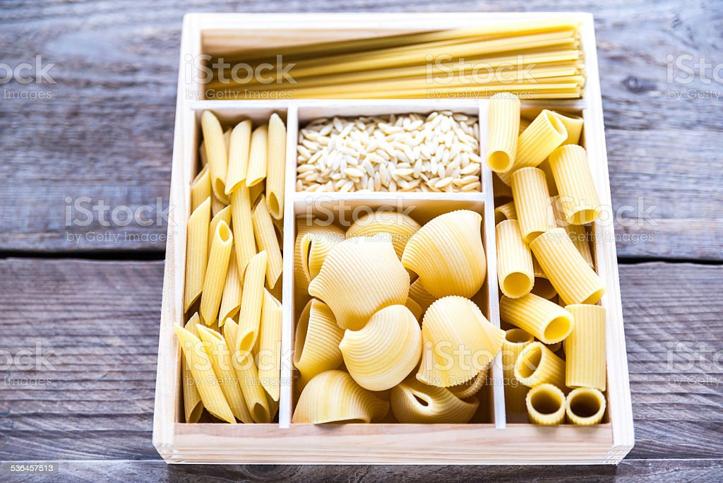 Various types of pasta in the wooden container stock photo