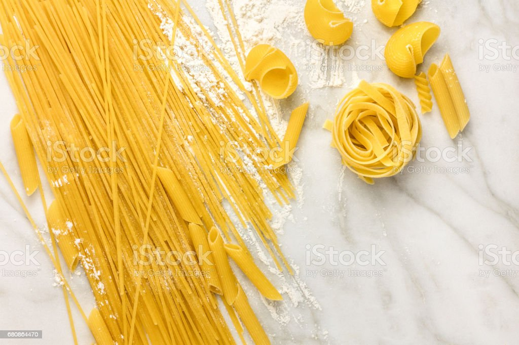 Various types of pasta on marble with copyspace royalty-free stock photo