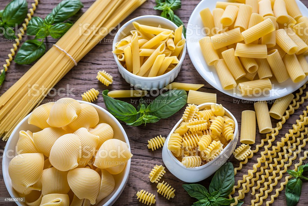 Various types of pasta on the wooden background stock photo