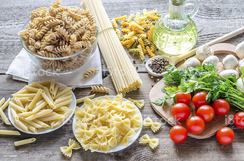 Various types of pasta with mushrooms and cherry tomatoes stock photo