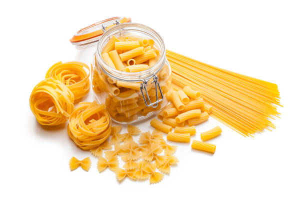 Various types of raw pasta isolated on white background Various types of raw pasta shot from above on white background. Types of pasta included in the composition are spaghetti, rigatoni, bow tie pasta and fettuccine. Predominant colors are yellow and white. High key DSRL studio photo taken with Canon EOS 5D Mk II and Canon EF 100mm f/2.8L Macro IS USM. uncooked pasta stock pictures, royalty-free photos & images