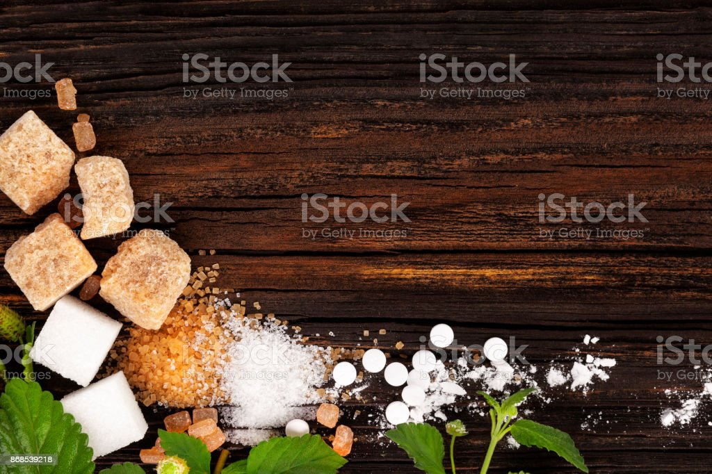 Various types of sugar from above on wooden table. stock photo
