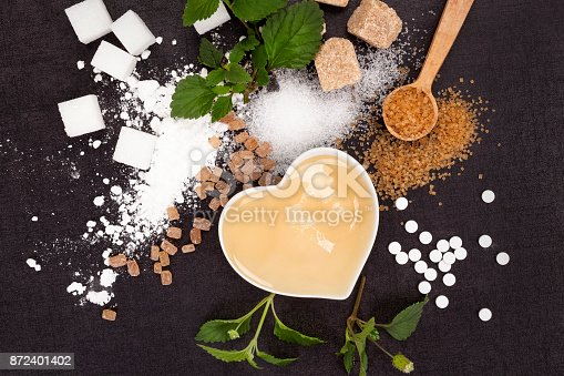 Various types of sugar from above - brown, white, crystal, cane, powdered sugar and artificial sweetener and honey in bowl. Aztec sweet herb.
