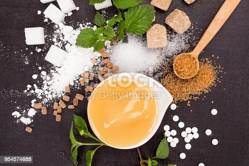Various types of sugar - brown, white, crystal, cane, powdered and artificial sweeteners with honey in bowl from above.