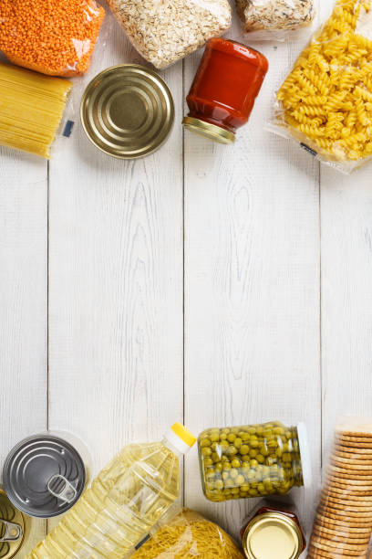 Various uncooked cereals, grains, pasta and canned food. Various uncooked cereals, grains, pasta and canned food on a white wooden table. Ingredients for cooking. Frame background with copy space. rice cereal plant stock pictures, royalty-free photos & images