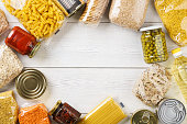 Various uncooked cereals, grains, pasta and canned food on a white wooden table. Ingredients for cooking. Frame background with copy space.