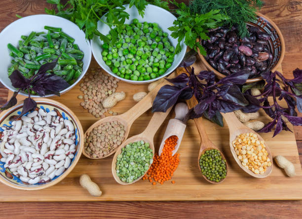 Various uncooked dried and frozen legumes and greens stock photo