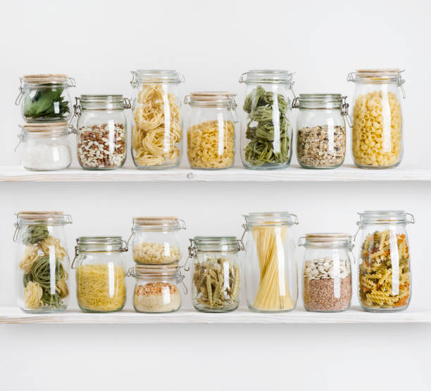 various uncooked groceries in glass jars arranged on wooden shelves - riso cereale foto e immagini stock