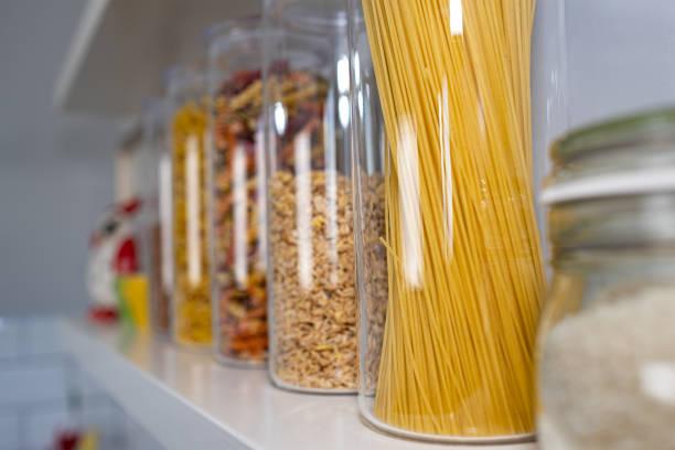verschiedene ungekochte lebensmittel in glasgefäßen, die auf holzregalen angeordnet sind - grundnahrungsmittel stock-fotos und bilder