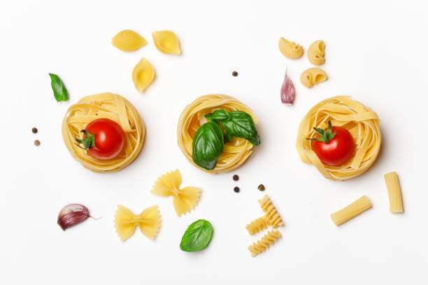 various uncooked pasta on white background. top view. raw pasta with ingredients for cooking. food concept - macarrão imagens e fotografias de stock
