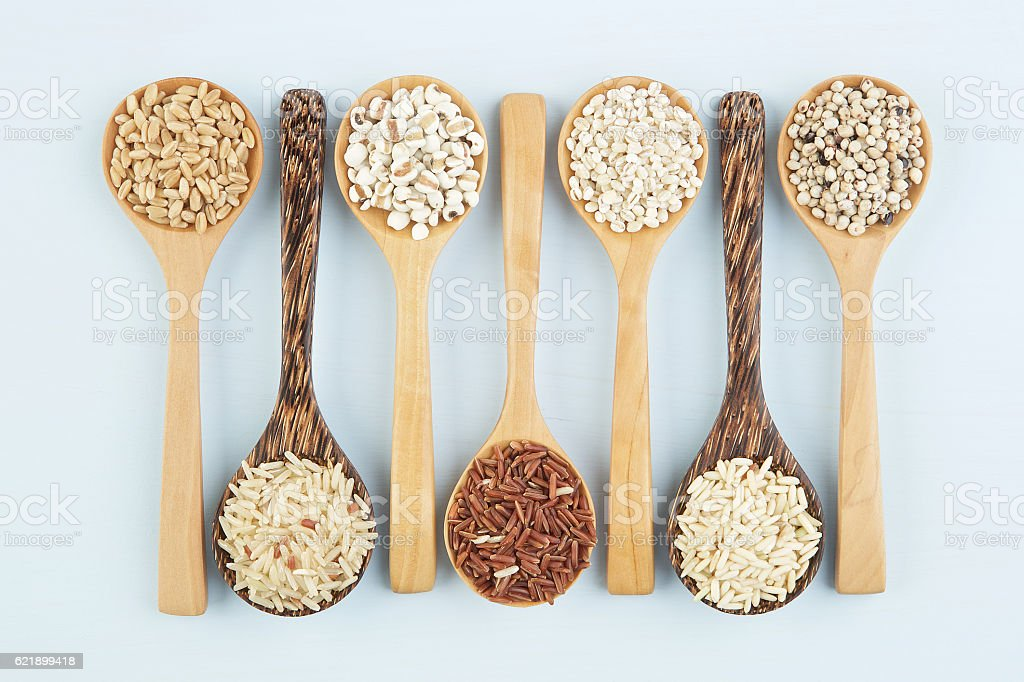 Various varieties of rice and wholegrains in spoon on wooden stock photo