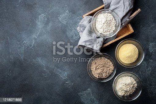 Various vegetable gluten free flour corn,sesame,oat,coconut in glass bowl on dark gray background. Alternative to wheat flour for keto paleo diet. Healthy eating,dieting food concept. Copy space,top view