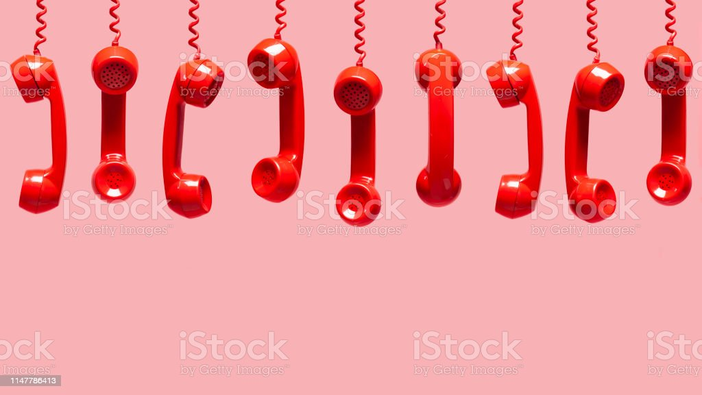 Various views of old red telephone receivers hanging on pink...