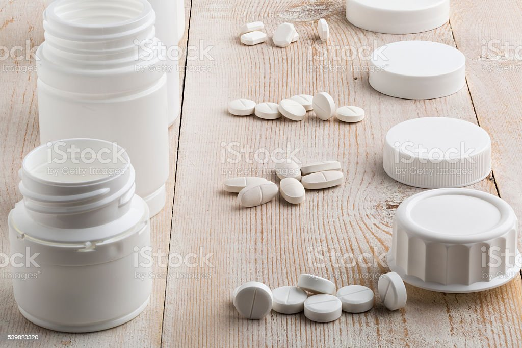 Various white plastic pill bottles and heap of drugs stock photo