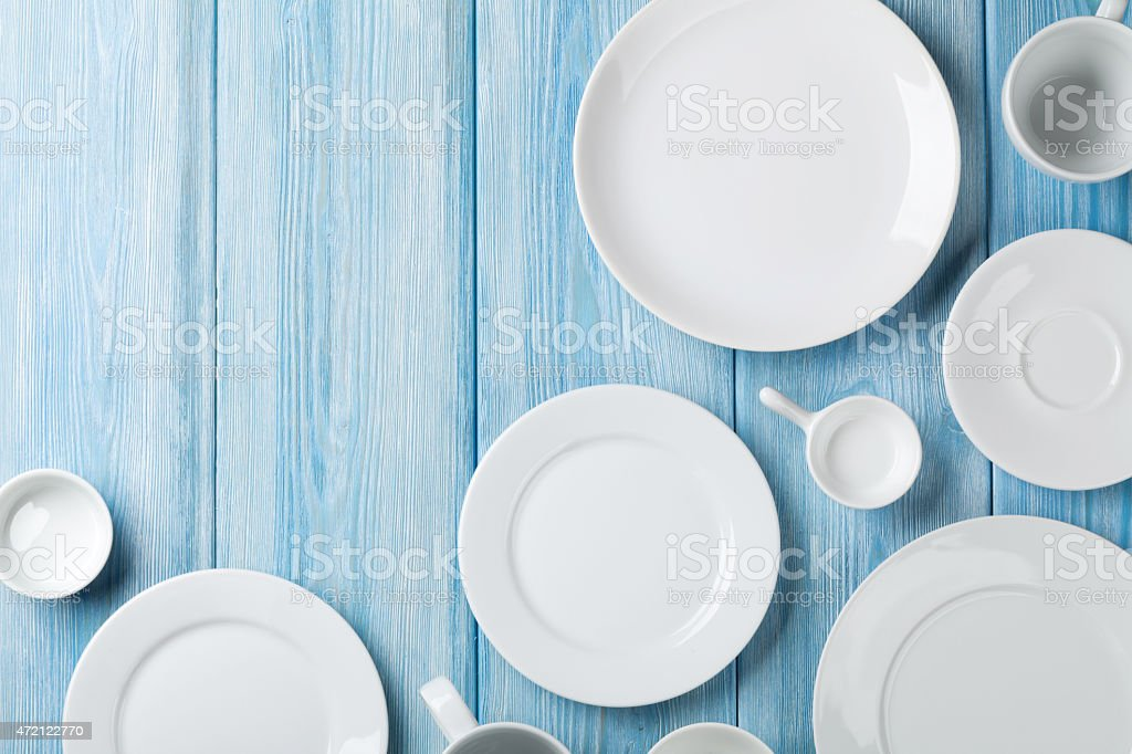 Various white plates, cups, and saucers on light blue wood  stock photo