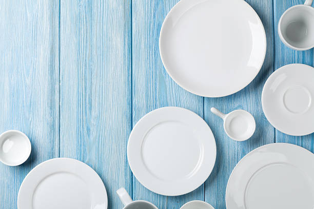 various white plates, cups, and saucers on light blue wood  - crockery stock photos and pictures