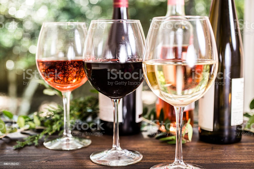 Various wine selections, glasses on outdoor dining table. Bottles. Nobody. stock photo